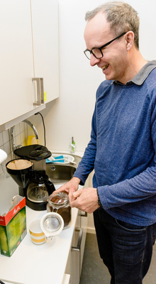 Álvaro Freitas Moreira makes coffee in the kitchen