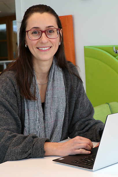 Photo of a woman sitting by a computer and smiling at the camera.