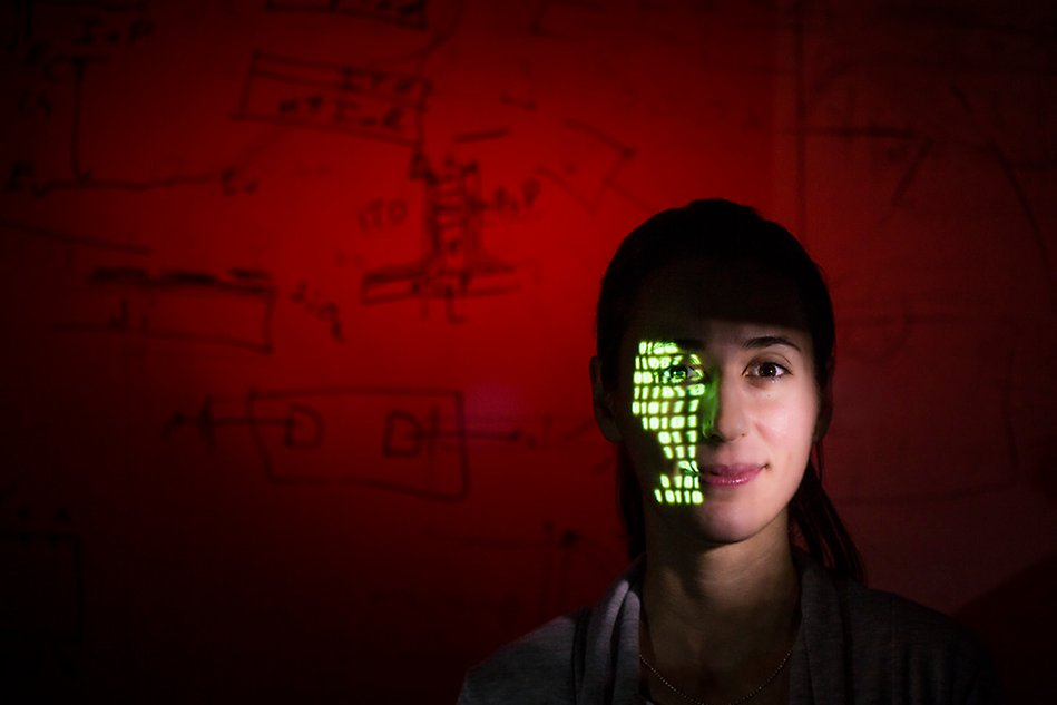 Picture of a woman with a projection of green light in the face.