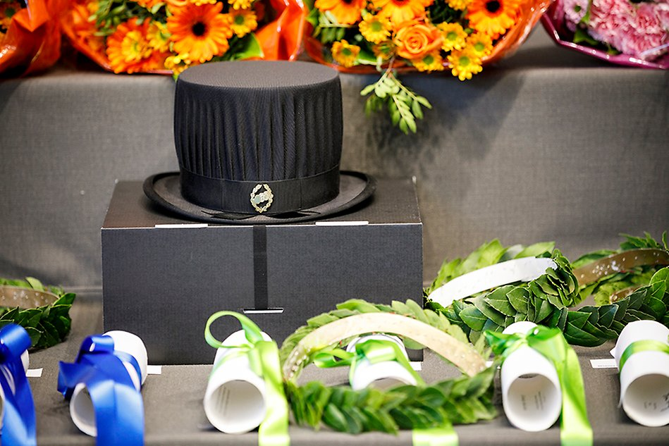 Table with doctoral hat, wreaths and diplomas wrapped with coloured ribbons