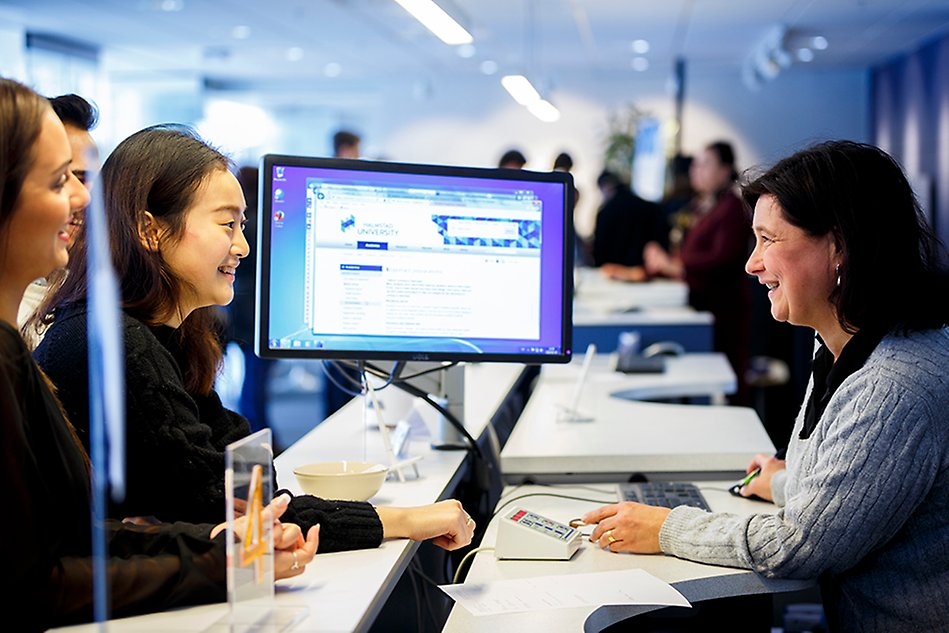 Woman at a service desk is showing two other people information on a computer monitor. Photo.