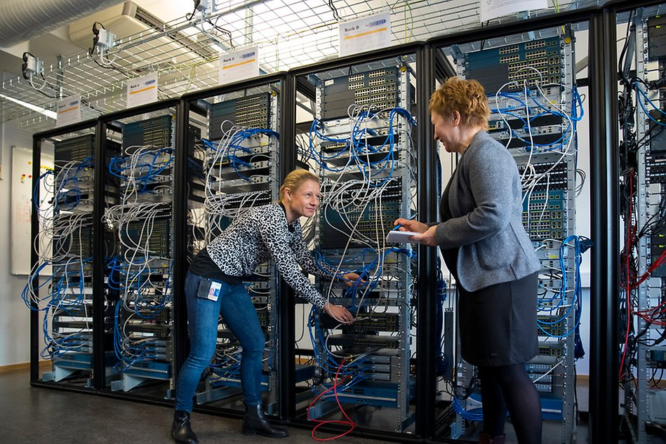 Two women stand in front of a server rack and show cords and computers. Photo.