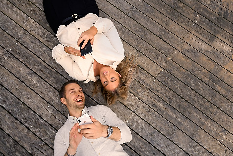A male and a female lying on a wooden floor with their mobile phones in their hands. Photo.