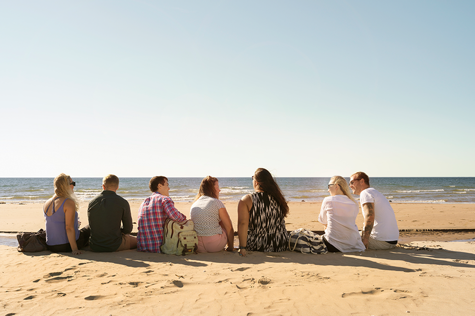 A group of people sitting on a beach, looking towards the ocean. Photo.