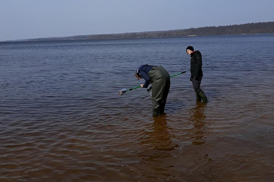 Two people standing in water taking samples. Photo.