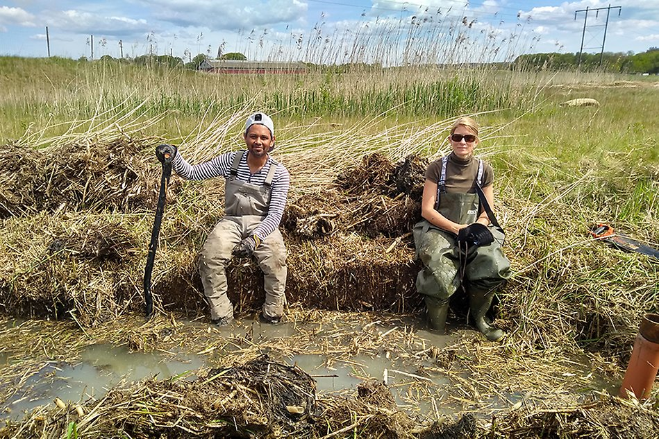 Two people sitting in a wetland