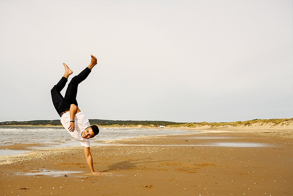A man is doing handstand on the beach. Photo.